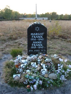 A Memorial for Margot and Anne Frank shows a Star of David and the full names and birthdates and year of death of each of the sisters, in white lettering on a large black stone. The stone sits alone in a grassy field, and the ground beneath the stone is covered with floral tributes and photographs of Anne Frank