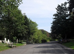 The approach road to the Woodvale cemetery, between high tree-lined banks, splits into three avenues which run through the valley between the graves.