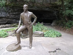 Statue of Jack Daniel in front of the spring from which he drew the water for producing his whiskey. The current production uses water drawn from about 150 yards further back from the grotto. (Jack Daniel's Distillery, Lynchburg, Tennessee)