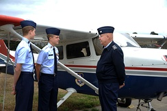 Two cadets speak to a senior member in front of a Cessna 172