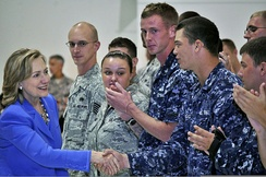 Clinton greeting U.S. military personnel at Andersen Air Force Base in Guam. The personnel are wearing uniforms and standing side by side.