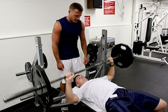 A man performs a barbell bench press while another spots him.