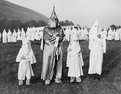 Two children wearing Ku Klux Klan robes and hoods stand on either side of Dr. Samuel Green, a Ku Klux Klan Grand Dragon, at Stone Mountain, Georgia on July 24, 1948.