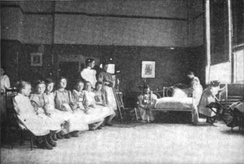 "Young girls learning how to make a bed at a ""vacation school"" in the late 1890s, what in modern terminology would probably be a summer camp."