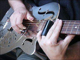 Example of a bottleneck, with fingerpicks and resonator guitar.