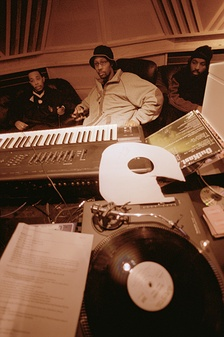 Hip hop producer and rapper RZA in a music studio with two collaborators. Pictured in the foreground is a synthesizer keyboard and a number of vinyl records; both of these items are key tools that producers and DJs use to create hip hop beats.