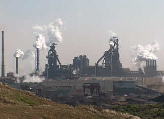 Integrated steel mill in the Netherlands. The two massive towers are blast furnaces.