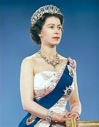 Queen Elizabeth II  in 1959 wearing the Vladimir tiara along with the Queen Victoria Jubilee Necklace, the blue Garter Riband, Badge and Garter Star and the Royal Family Orders of King George V and King George VI.