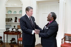 "U.S. President Ronald Reagan meeting with Desmond Tutu in 1984. Tutu described Reagan's administration as ""an unmitigated disaster for us blacks"",[168] and Reagan himself as ""a racist pure and simple""[169]"