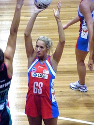Erin Bell from the New South Wales Swifts (red) prepares to shoot for a goal against the Melbourne Vixens.