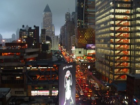 "Eighth Avenue, looking northward (""Uptown""), in the rain; most streets and avenues in Manhattan's grid plan incorporate a one-way traffic configuration"