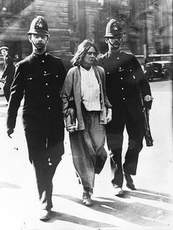 A woman under arrrest walking between two policemen