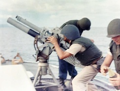 A gun crew on board USCGC Point Comfort (WPB-82317) firing an 81mm mortar during the bombardment of a suspected Viet Cong staging area one mile behind An Thoi in August 1965