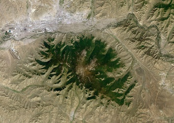 A satellite image, showing Bogd Khan Mountain in the center, Ulaanbaatar in the northwest corner, Tuul River running between the city and the mountain, the town of Zuunmod south of the mountain, the town of Nalaikh east of the mountain, and Chinggis Khaan International Airport west of the mountain