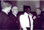 Frocking ceremony for U.S. Navy's first Muslim chaplain, when Navy (rabbi) Chaplain Arnold Resnicoff attaches new shoulder boards with Muslim Chaplain crescent insignia to uniform of Imam Monje Malak Abd al-Muta Noel Jr, 1996.