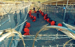 "Captives at Camp X-Ray, Guantanamo Bay, Cuba, a United States military prison where people are being indefinitely detained in solitary confinement as part of the ""War on Terror"" (January 2002). The prisoners are forced to wear goggles and headphones for sensory deprivation and to prevent them from communicating with other prisoners."