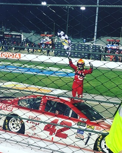 Larson raises the checkered flag in the air after winning the 2017 Federated Auto Parts 400 for his fourth win of 2017, and fifth win of his career.