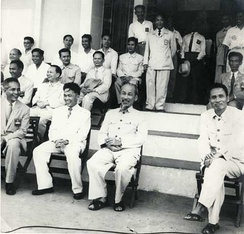 Hồ Chí Minh watching a football game in his favorite fashion, with his closest comrade Prime Minister Phạm Văn Đồng seated to Ho's left (photo right)
