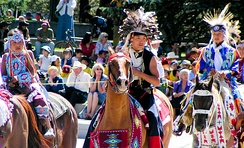 Colour photograph of Tsuu T'ina children in traditional costume on horseback at a Stampede Parade in front of an audience