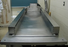 Cadaver dissection table similar to those used in medical or forensic autopsies.