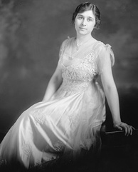 A slightly-built, dark haired woman wearing a white dress and leaning backward onto her left arm