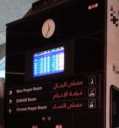 A sign detailing departing flights, as well as indicating the location of a dedicated ihram room in Queen Alia international airport, Amman, Jordan