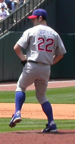"A view of a man in a grey baseball jersey on a mound of dirt preparing to throw a pitch. The back of his jersey says ""Prior"", with the number 22."