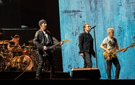 Four men performing on a stage in front of a crowd; two are standing at the front of the stage holding guitars, one in the center is holding a microphone, and one is sitting behind a drum set.