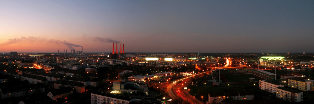 Wolfsburg panorama at dusk, viewed from Schillerteich-Center. The red-lit chimneys left of the center belong to the Volkswagen plant.