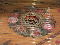Detail of the harpsichord by Karl Conrad Fleischer; Hamburg, 1720 in Museu de la Música de Barcelona. A decorative rose descends below the soundboard in which it is mounted; the soundboard itself is adorned with floral painting around the rose. The bridge is at lower right.