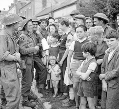 Members of the Green Howards (of either the 6th or 7th Battalions) talking to French civilians, 23 August 1944.
