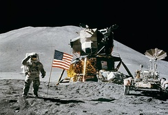 Astronaut James Irwin walking on the Moon next to Apollo 15's landing module and lunar rover in 1971. The effort to reach the Moon was triggered by the Space Race.