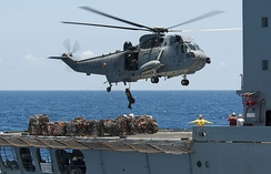 A CH-124 Sea King lowers a crewman onto the deck of USNS Yukon during RIMPAC 2012