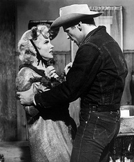 Monroe and Don Murray in Bus Stop. She is wearing a ragged coat and a small hat tied with ribbons and is having an argument with Murray, who is wearing jeans, a denim jacket and a cowboy hat.