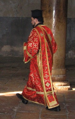 Greek Orthodox deacon in the Church of the Nativity in Bethlehem, wearing an orarion over his sticharion. On his head he wears the clerical kamilavka.