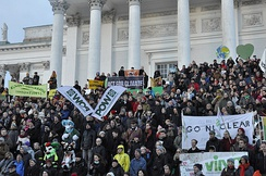 "Many people standing on steps of large public building holding banners with signs, including ""Act For Climate"" and ""Go Nuclear."""