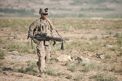 U.S. Army Pfc. Michael Andrade, an infantryman with Bravo Company, 3rd Battalion, 15th Infantry Regiment, 4th Infantry Brigade Combat Team, 3rd Infantry Division, carries an M240B machine gun while on a foot patrol near Combat Outpost Soltan Khel in Wardak province, Afghanistan, 6 June 2013