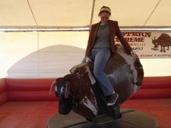 A woman riding on a mechanical bull