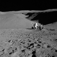 Lunar landscape with man leaning over rover