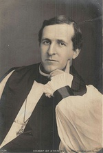 Black-and-white photo of a dark-haired white man, seated and resting his left hand around his chin, dressed in bishop's robes (rochet and chimere, pectoral cross and clerical shirt)