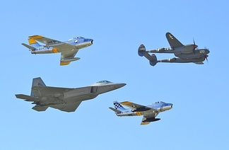 U.S. Air Force fighter aircraft representing different eras; a World War II P-38 Lightning (upper-right), a pair of F-86 Sabres from the early jet age and a modern F-22 Raptor (lower-left)