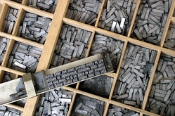 Movable type being assembled on a composing stick using pieces that are stored in the type case shown below it