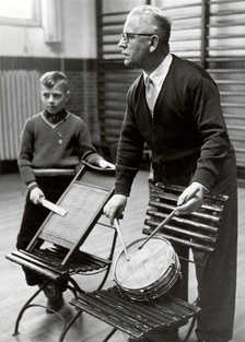 An elementary music teacher instructing a child in 1957 in the Netherlands.