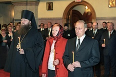 Lyudmila Putina wearing a headscarf next to Vladimir Putin while attending a commemoration service for the victims of terrorist attacks, November 16, 2001