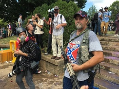 An attendee at the Unite the Right rally carrying a firearm and wearing a Confederate Battle Flag T-shirt.