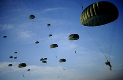 Soldiers with the 82nd Airborne Division descend under a parachute canopy to earn foreign jump wings during the 11th Annual Randy Oler Memorial Operation Toy Drop at Fort Bragg, North Carolina, 6 December 2008.