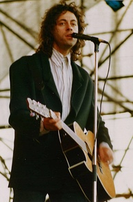 Bob Geldof, a Caucasian man in his mid-thirties, is on stage, singing into a microphone and playing a left-handed acoustic guitar. He wears a white shirt and a dark green jacket.