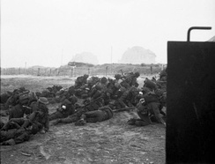 British troops take cover after landing on Sword Beach.