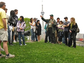 A Jane's Walk group pauses at Fort York National Historic Site in Toronto