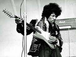 A black and white photograph of a man playing an electric guitar.